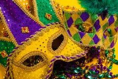 Gruppe von Mardi Gras Masks auf gelbem Hintergrund mit Perlen lizenzfreies stockfoto