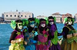 Gruppe von Personen in den bunten Kostümen und in den Masken, Ansicht über Grand Canal Lizenzfreie Stockfotografie