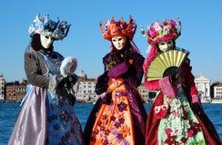 Gruppe von Personen in den bunten Kostümen und in den Masken, Ansicht über Grand Canal Lizenzfreie Stockfotos