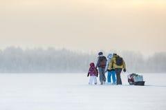Gruppe von Personen, die über Eis von gefrorenem See durch das Schneien zur Winterzeit reist Lizenzfreie Stockfotografie
