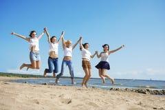 Gruppe von Personen, die auf dem Strand sich entspannt Stockbilder