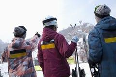 Gruppe von Personen, die auf Hügel in Ski Resort zeigt Stockbild