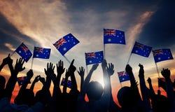 Gruppe von Personen, die australische Flaggen in hintergrundbeleuchtetem wellenartig bewegt Lizenzfreie Stockfotografie