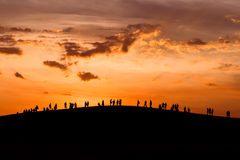 Gruppe von Personen, die den Sonnenuntergang auf Hügel genießt Stockfotos