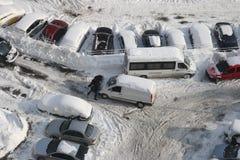 Gruppe von Personen, die ein Auto im Schnee drückt Stockbild