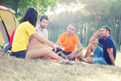 Gruppe von Personen, die eine Geschichte kampiert und erklärt stockbilder