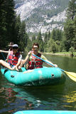 Gruppe von Personen, die hinunter den Fluss flößt Stockfoto