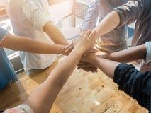Gruppe von Personen, die ihre Hände zusammenarbeiten auf hölzernen Hintergrund in Büro einsetzt Gruppenstützteamwork-Zusammenarbe