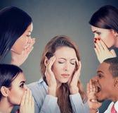 Gruppe von Personen, die Klatsch zu einer betonten Frau leidet unter Kopfschmerzen flüstert stockfotos