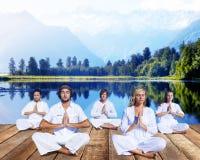 Gruppe von Personen, die Meditation nahe Gebirgszug tut Stockfotos