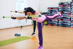 Gruppe von Personen, die mit fitbars am Fitness-Club excercising ist Stockfoto