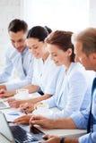 Gruppe von Personen, die mit Laptops im Büro arbeitet Lizenzfreie Stockfotografie