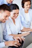 Gruppe von Personen, die mit Laptops im Büro arbeitet Stockfoto