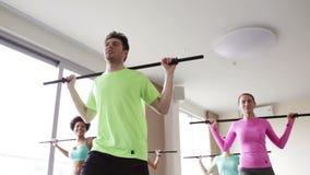 Gruppe von Personen, die mit Stangen in der Turnhalle trainiert stock video