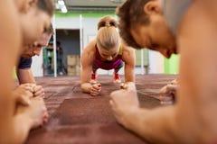 Gruppe von Personen, die Plankenübung in der Turnhalle tut Stockfotos