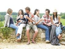 Gruppe von Personen, die sich draußen mit Kaffee entspannt Lizenzfreies Stockbild