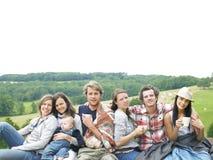 Gruppe von Personen, die sich draußen mit Kaffee entspannt Stockbild