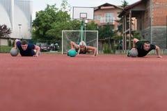 Gruppe von Personen, die Stoß-UPS auf Medizinball ausübt Stockfoto