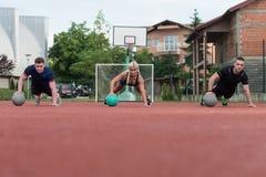 Gruppe von Personen, die Stoß-UPS auf Medizinball ausübt Lizenzfreies Stockbild