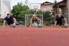 Gruppe von Personen, die Stoß-UPS auf Medizinball ausübt Stockfotos