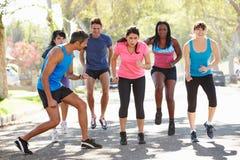 Gruppe von Personen, die Straße mit persönlichem Trainer ausübt Lizenzfreie Stockfotos