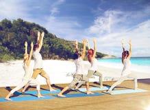 Gruppe von Personen, die Yogaübungen auf Strand macht Stockfotos
