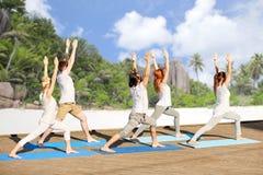 Gruppe von Personen, die Yogaübungen auf Strand macht Stockbild
