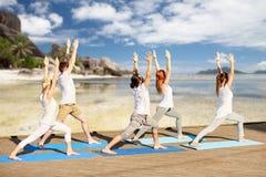 Gruppe von Personen, die Yogaübungen auf Strand macht Stockfotografie