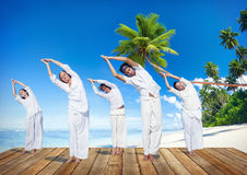 Gruppe von Personen, die Yoga auf Strand tut Stockfoto