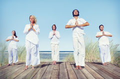 Gruppe von Personen, die Yoga auf Strand tut Stockbild