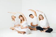 Gruppe von Personen, die Yoga im Weiß sich entspannt und tut Lizenzfreie Stockfotografie