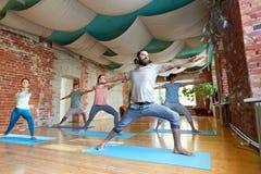 Gruppe von Personen, die Yogakriegershaltung am Studio tut Stockbilder