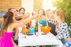 Gruppe von Personen, die zusammen das Mittagessen und das Rösten habend sitzt Lizenzfreies Stockfoto