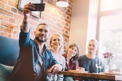 Gruppe von Personen, die zusammen ein selfie in einem Restaurant nimmt stockfotos