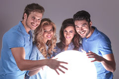 Gruppe von Personen mit den Händen auf großem Ball des Lichtes Lizenzfreie Stockbilder