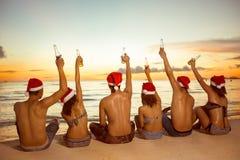Gruppe von Personen mit Sankt-Hüten, die auf sandigem Strand sitzen lizenzfreies stockbild