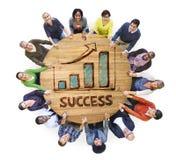 Gruppe von Personen um Holztisch mit Erfolg lizenzfreies stockfoto