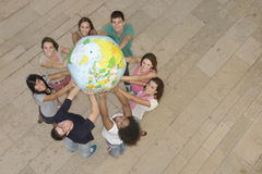 Gruppe von Personen, welche die Erde-Kugel anhält stockbild