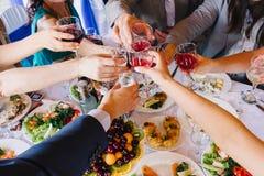 Gruppe von Personenen-Geklirrgläser mit Rot und Weißwein Lizenzfreie Stockfotos