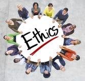 Gruppe von Personenen-Händchenhalten um Buchstabe-Ethik Lizenzfreies Stockbild