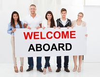Gruppe von Personenen-Holding-Willkommen an Bord des Plakats stockfotografie