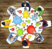 Gruppe von Personenen-Sitzung mit Glühlampe-Symbol Lizenzfreie Stockfotos
