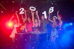 Gruppe von Personenen-Tanzen am Nachtclub mit Sankt-Hut Weihnachtsfeiertagspartei Stockfoto