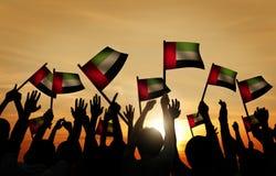 Gruppe von Personenen-wellenartig bewegende Flagge von UAE in hintergrundbeleuchtetem lizenzfreies stockbild