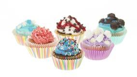 Gruppe von sechs verschiedenen bunten kleinen Kuchen lokalisiert Lizenzfreie Stockfotos