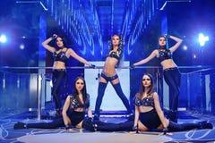 Gruppe von sexy gehen-gehen die Tänzer, die schwarze Ausstattungen tragen Stockfotos
