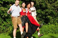 Gruppe von vier Freunden im bayerischen Tracht Tanzen Lizenzfreies Stockbild