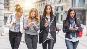 Gruppe von vier Freundinnen mit Smartphones auf der Straße Stockbild