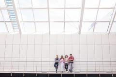 Gruppe von vier jungen lächelnden Leuten, welche die stilvolle Freizeitbekleidung betrachtet die Kamera steht im hellen Büro oder lizenzfreie stockfotografie