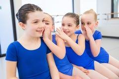 Gruppe von vier jungen Mädchen, die zusammen Geheimnissen sagen Stockbild
